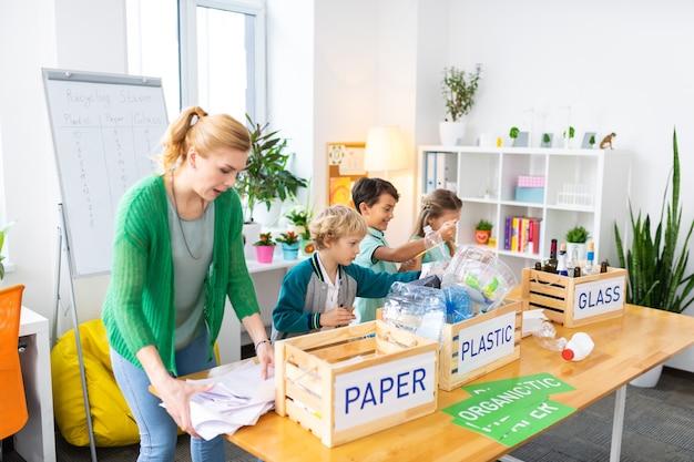 A proposito di sprechi di cernita. insegnante che indossa un cardigan verde che racconta ai bambini di sprecare problemi di smistamento ed ecologia