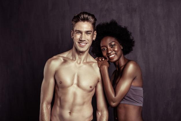 Felicità assoluta. felice coppia multietnica che sorride mentre si sente benissimo insieme