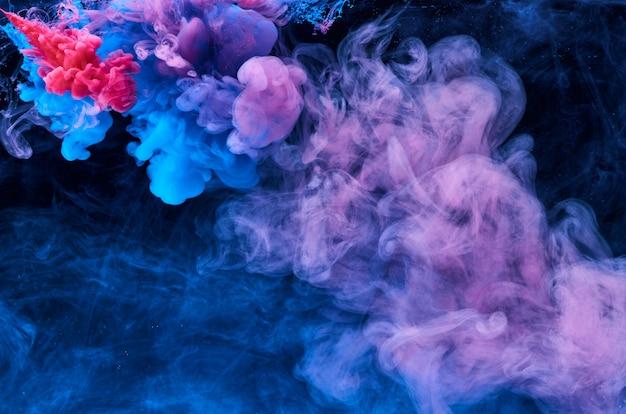 Turbinii astratti di colore della vernice acrilica in acqua, colpo da sotto, sfondo nero. sfondo astratto macchia d'inchiostro