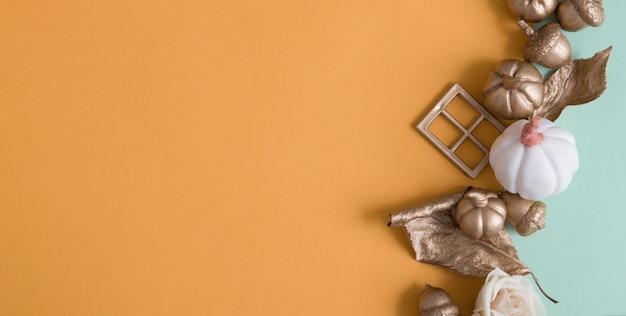 Astratto sfondo autunnale con zucche dorate, foglie, ghiande su fondali di carta colorata con spazio copia in formato banner
