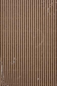 Fondo astratto di struttura beige del cartone ondulato, disposizione piana. fondale marrone ruvido con spazio libero per il testo.