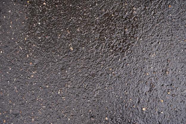 Sfondo astratto di asfalto bagnato nero con inclusioni di ciottoli