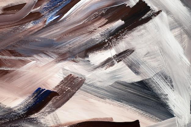Sfondo astratto caoticamente imbrattato di vernice acrilica. immagine di un marrone scuro, beige, bianco e nero pennellate con texture di stucco bagnato.