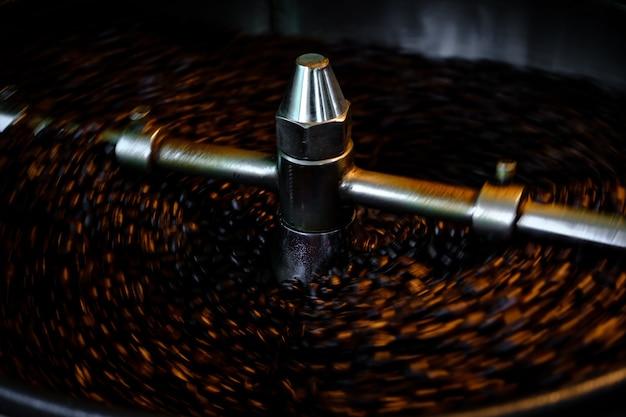 Sfondo astratto chicchi di caffè in macchina arrosto e close up fuoco selettivo lunga esposizione girato sfondo sfocatura movimento.