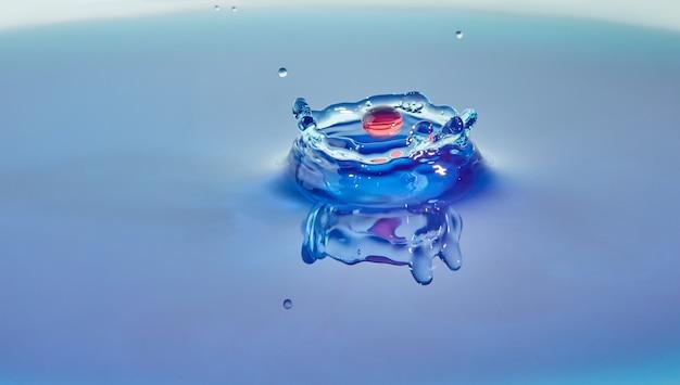 Spruzzi d'acqua di colore di sfondo astratto, collisione di gocce colorate e creazione di una corona, concept art con effetto astratto.