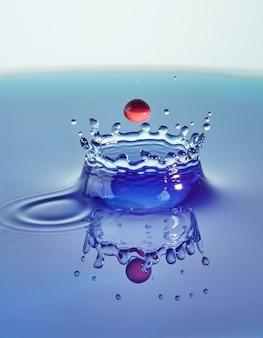 Spruzzi d'acqua di colore di sfondo astratto, collisione di gocce colorate e creazione di una corona