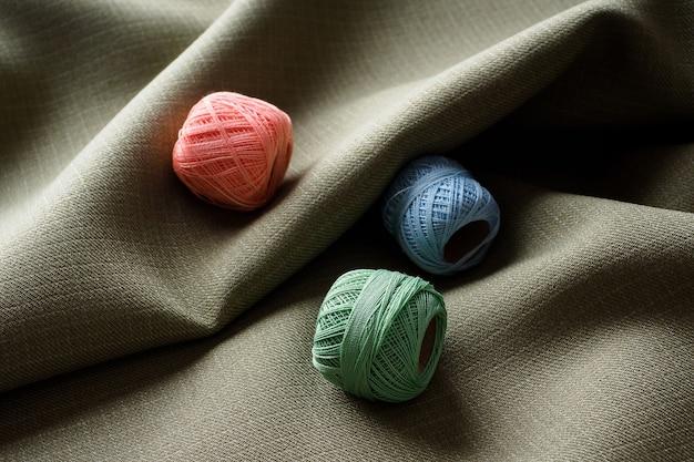 Sfondo astratto, bellissimo tessuto scuro curvo e bobine con diversi fili colorati, spazio per copie. cucire il concetto di minimalismo. il tessuto grigio drappeggiato si trova in una bella onda.
