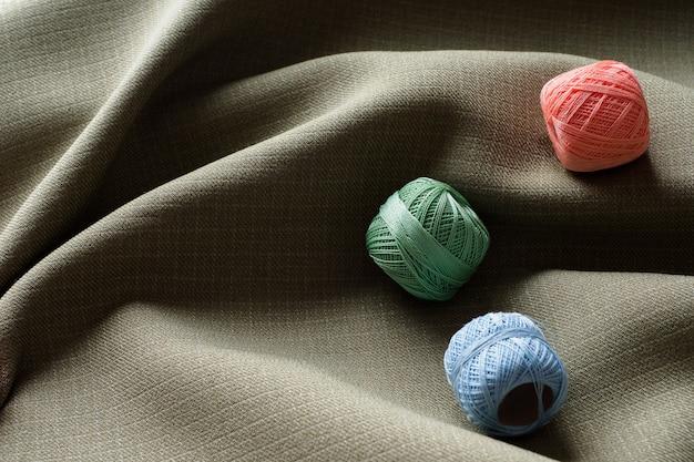 Sfondo astratto, tessuto bello scuro curvo e bobine con fili colorati diversi, spazio di copia.