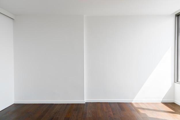 Priorità bassa astratta dal muro di cemento bianco in bianco a casa o in ufficio con pavimento in legno.