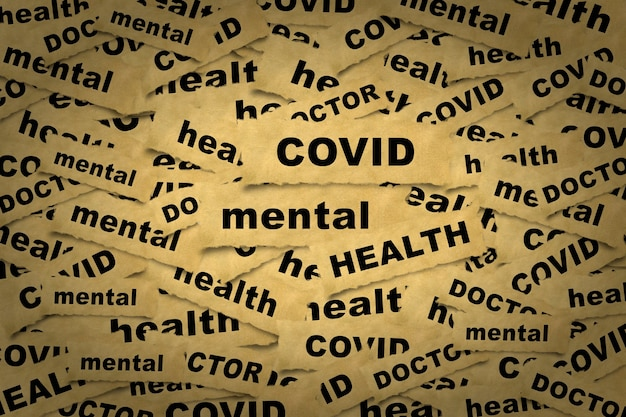 Sfondo astratto da pezzi di carta con l'iscrizione covid salute mentale e parole correlate.