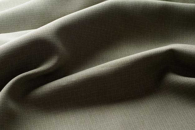 Sfondo astratto, tessuto lussuoso grigio si trova in pieghe ondulate, primo piano. design elegante.