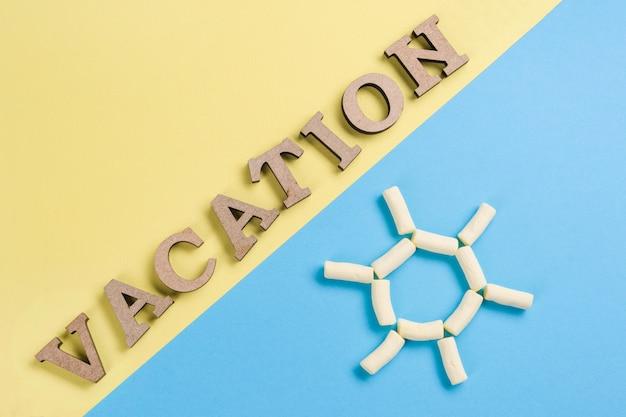 Immagine di sfondo astratto. esprima le lettere di legno di vacanza su un fondo blu e giallo e una parete astratta del sole.