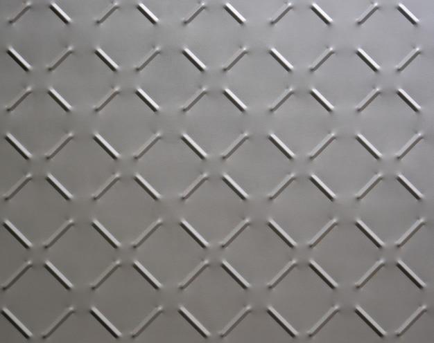 Sfondo astratto di piastra metallica con motivo a rombi dipinto di grigio vicino.