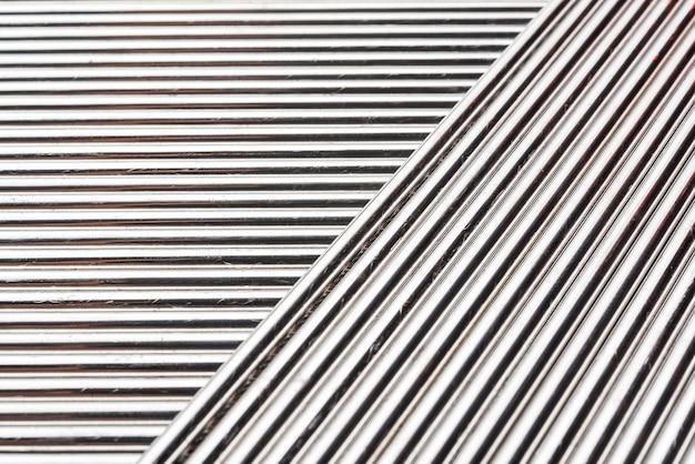 Sfondo astratto di bacchette per saldatura in acciaio inox, su sfondo nero