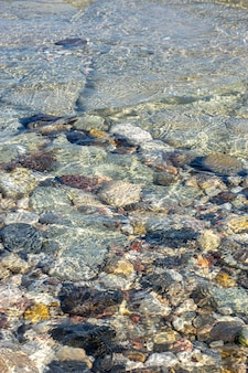 Texture di sfondo astratto, pietre di mare colorate in acqua, vista dall'alto