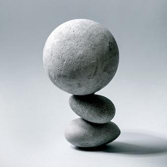 Sfondo astratto con composizione di oggetti geometrici grigi equilibrati sfera e pietre. copia spazio. concetto moderno per la presentazione del prodotto. piazza