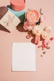 Sfondo astratto con fiori, scatole regalo e un modello per carte, inviti in colori tenui pastello.