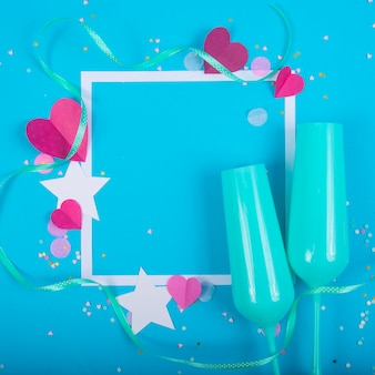 Sfondo astratto con cuori di carta, cornice, bicchieri di champagne blu per san valentino.