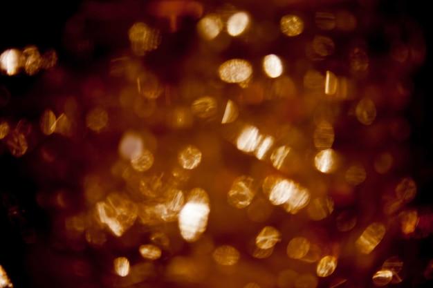 Astratto sfondo nero, luci bolla d'oro o fiocchi di neve che cadono di notte