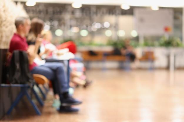 Sfocatura dello sfondo astratto di persone o passeggeri seduti nel terminal di trasporto dell'aeroporto