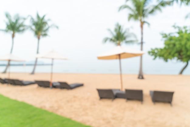 Sfocatura astratta sedia da spiaggia sulla spiaggia con mare oceano per lo sfondo - concetto di viaggio e vacanza