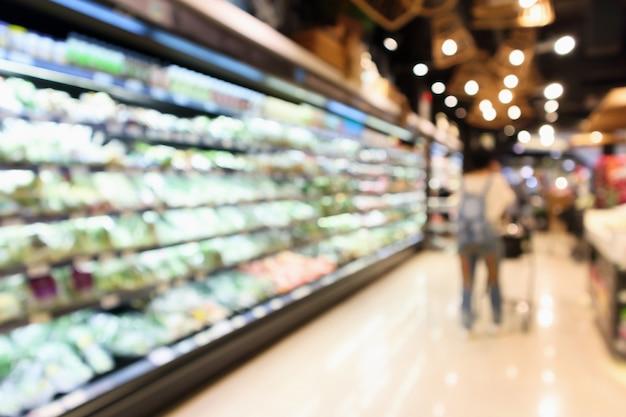 La sfuocatura astratta organica frutta fresca e verdura sugli scaffali della drogheria nel supermercato sfocato bokeh sfondo chiaro