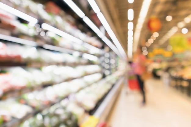 Sfocatura astratta frutta e verdura fresche organiche sugli scaffali della drogheria nel negozio di supermercati sfocati sullo sfondo della luce del bokeh