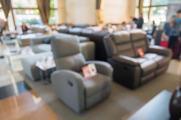 Sofà astratto della sfuocatura nell'interno del negozio della sala d'esposizione della mobilia della decorazione domestica con il fondo della luce del bokeh per l'esposizione del prodotto del montaggio