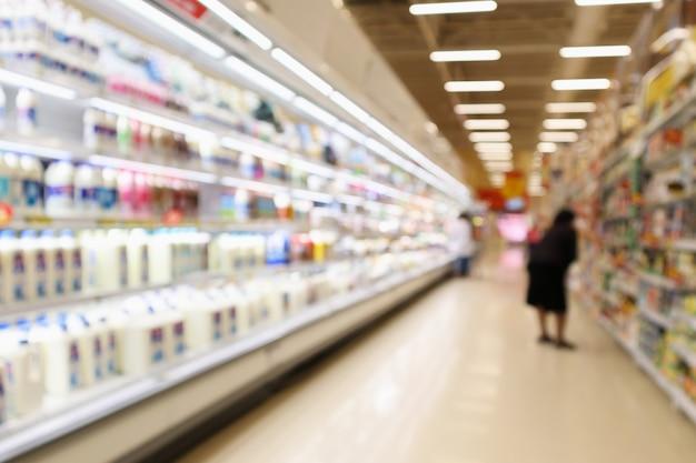 Scaffali del frigorifero della drogheria del supermercato della sfuocatura astratta con le bottiglie di latte fresco e i prodotti lattiero-caseari