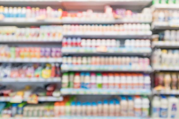 Scaffali del frigorifero della drogheria del supermercato della sfuocatura astratta con bottiglie di latte fresco e prodotti lattiero-caseari