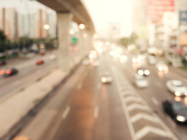 Immagine astratta di sfondo offuscata di traffico di sera su strada, sfocatura di veicoli automobili, saloon, autobus, moto, persone in strada - fuori concetto di fuoco nella città bangkok tailandia.