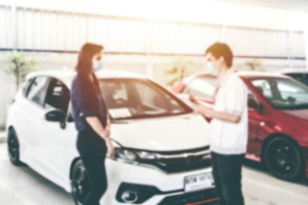 La gente vaga astratta sta donna che parla con l'ufficiale dell'uomo con il fondo dell'automobile. manutenzione auto e concetto di riparazione. concetto di conversazione.