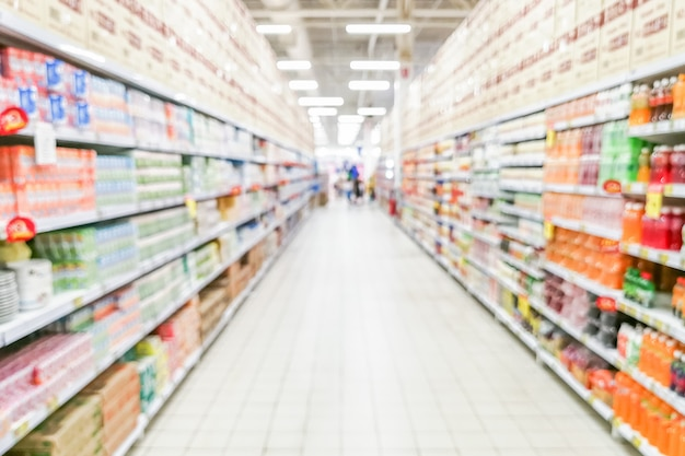 Estratto navata supermercato offuscata con ripiani colorati e clienti irriconoscibili
