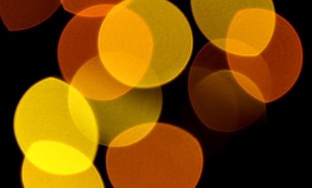 Abstract offuscata vibrante colore giallo e arancio luce illuminata su sfondo scuro