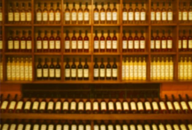 Abstract sfocato di bottiglie di vino visualizzate sullo scaffale di legno per sfondo o carta da parati
