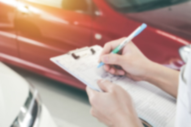 Mano ravvicinata sfocata astratta di uomini che controllano o scrivono su carta con sfondo auto. manutenzione auto e concetto di riparazione.