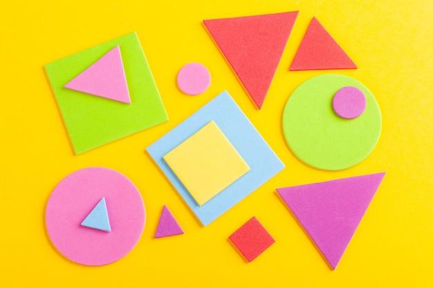 Fondo luminoso astratto di figure geometriche colorate, tagliato da carta su giallo