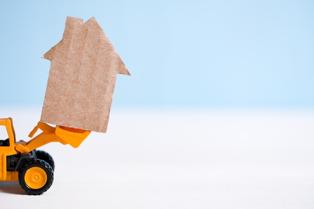 Casa astratta del cartone su macchinario di costruzione. costruzione di alloggi chiavi in mano.
