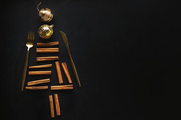 Albero di natale astratto con coltello e forchetta, bastoncini di cannella e palline di natale sul nero. lay piatto.
