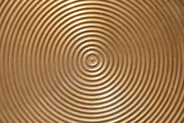 Superficie di piastra metallica-dorata astratta del cerchio con linee rotonde.