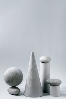 Composizione astratta di diversi oggetti geometrici grigi e pietre. copia spazio. concetto moderno per la presentazione del prodotto.