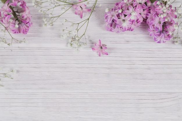 La composizione astratta dei fiori viola freschi del giacinto su una superficie di legno rustica bianca. modello di fiori diversi. superficie floreale delicata primaverile, cartolina di vacanza. spazio piatto per il testo