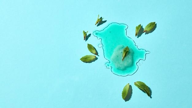 Composizione astratta di gelato fuso su uno sfondo di vetro blu con foglie di menta confini chiari e riflessione. vista dall'alto