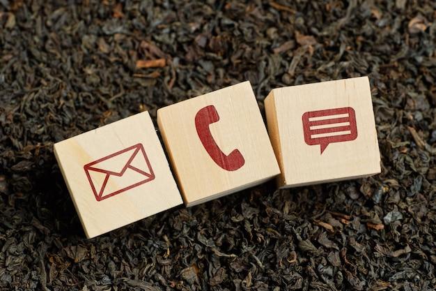 Icone astratte del contatto - busta, telefono, messaggio - sui cubi di legno e sul tè asciutto.
