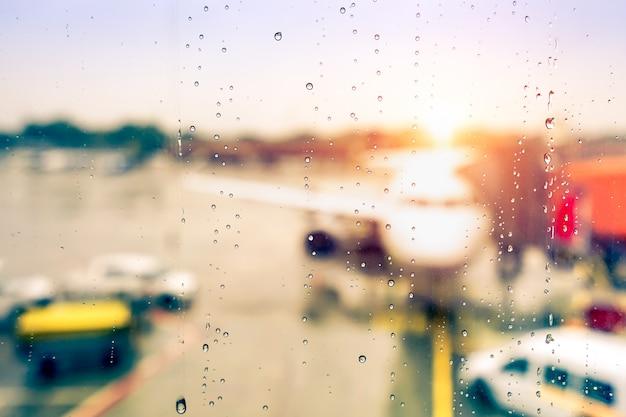 Bokeh sfocato astratto dell'aeroplano al cancello dell'aeroporto con il sole che esce dopo la pioggia
