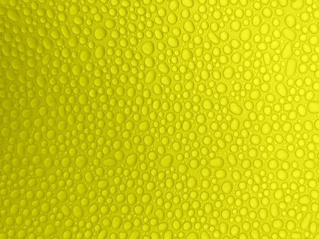 Astratte gocce d'acqua su uno sfondo giallo. gocce di pioggia.
