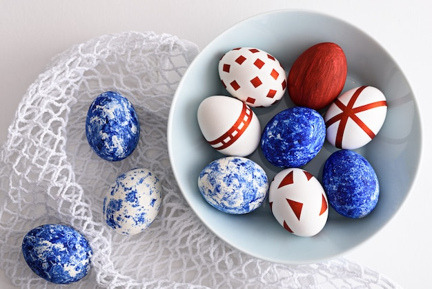 Uova di pasqua astratte con motivi geometrici rossi e nel colore del blu classico dell'anno nel piatto blu su borsa ecologica in rete bianca.