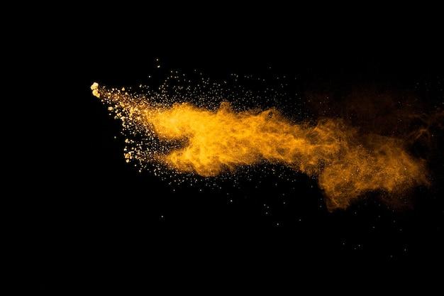 Esplosione astratta di polvere arancione su sfondo nero. congelare il movimento dello scoppio di polvere arancione.
