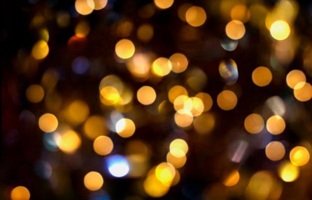 Fondo vago festivo astratto delle luci dorate del bokeh sul nero