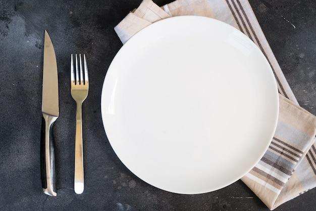 Sfondo astratto cibo vuoto piatto bianco con tovagliolo di lino e posate